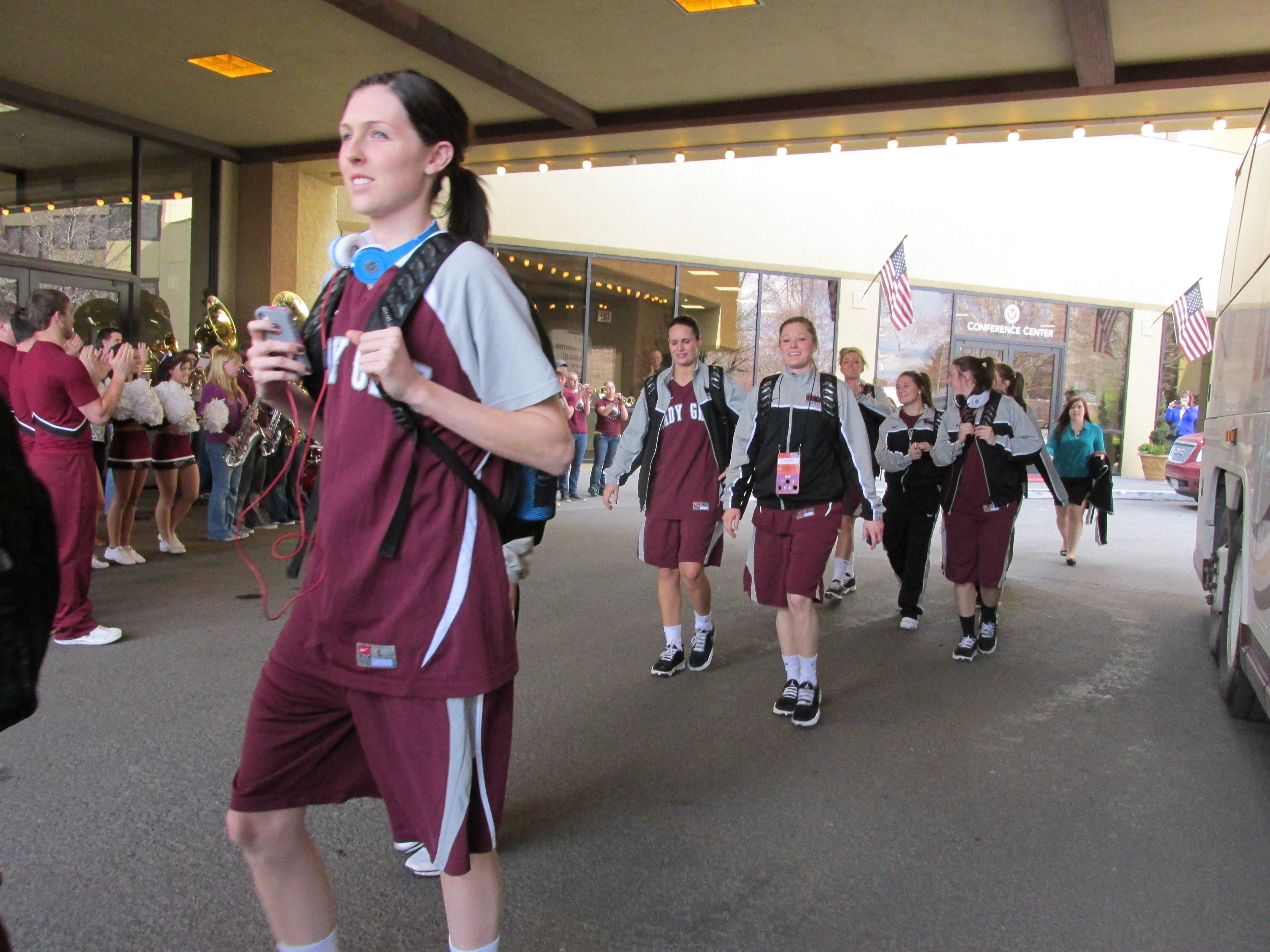 The Lady Griz walking to the bus while the band plays and the cheer squad cheers.