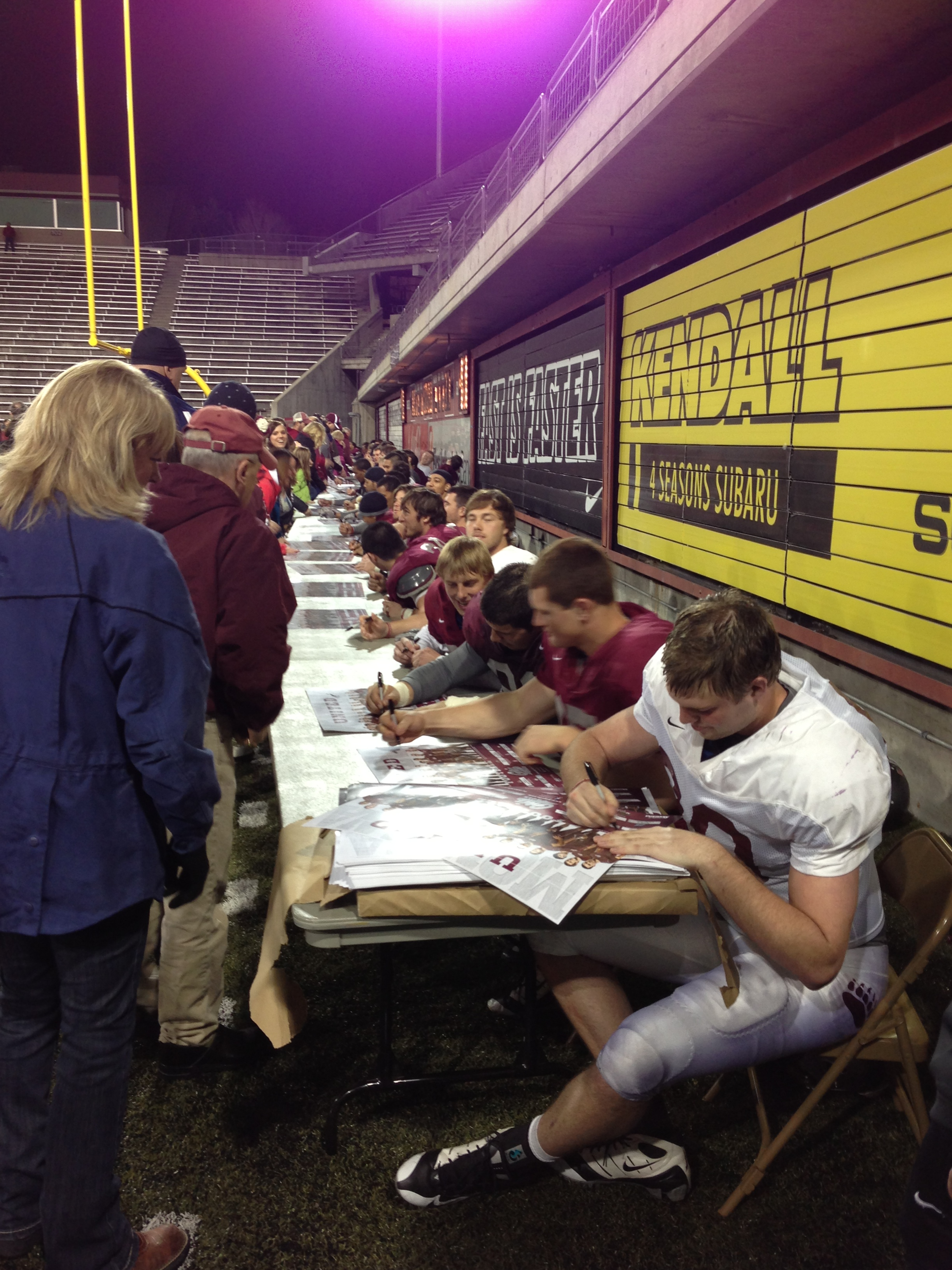 The football team signs autographs under the lights.