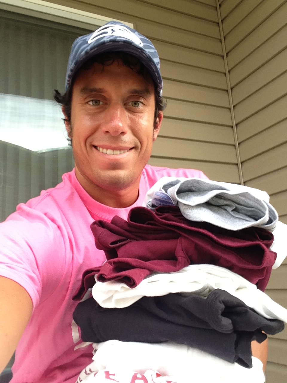 Me with a stack of t-shirts that I own from work. I am wearing a Play 4 Kay shirt in this photo.