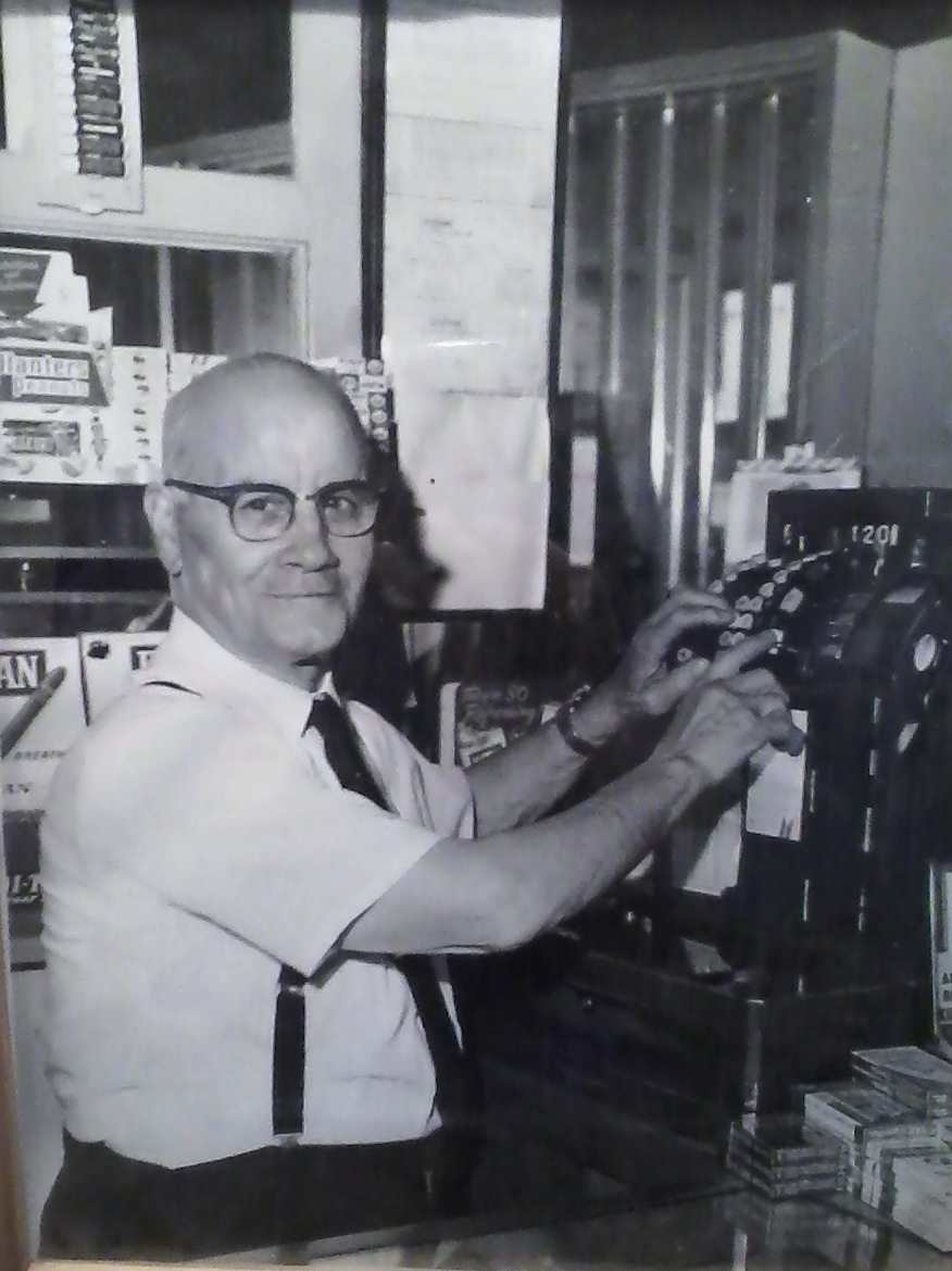 This is my great grandpa at the cash register. As you can barely see, the glass counter case is visible at the very bottom of the picture. The wooden door is also visible.