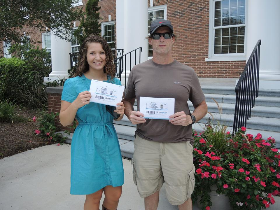 Marisa and her dad, Darryl, with the game tickets they won on Saturday afternoon.