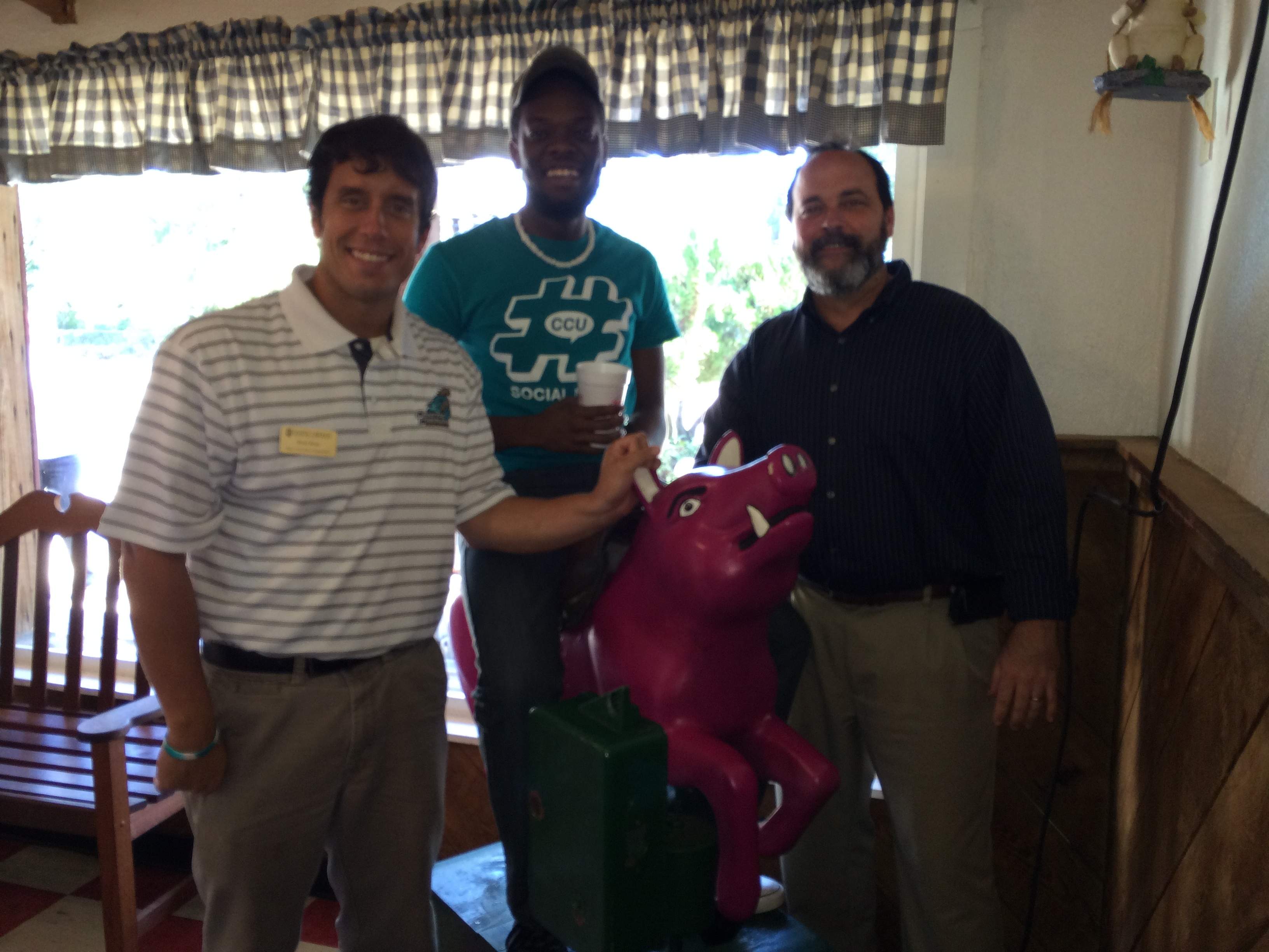 "The three birthday boys next to a pink pig. Our student graphic worker in the middle is Daniel ""Scoops"" Mableton and our Director of Creative Services, Rob Wyeth, is on the right."