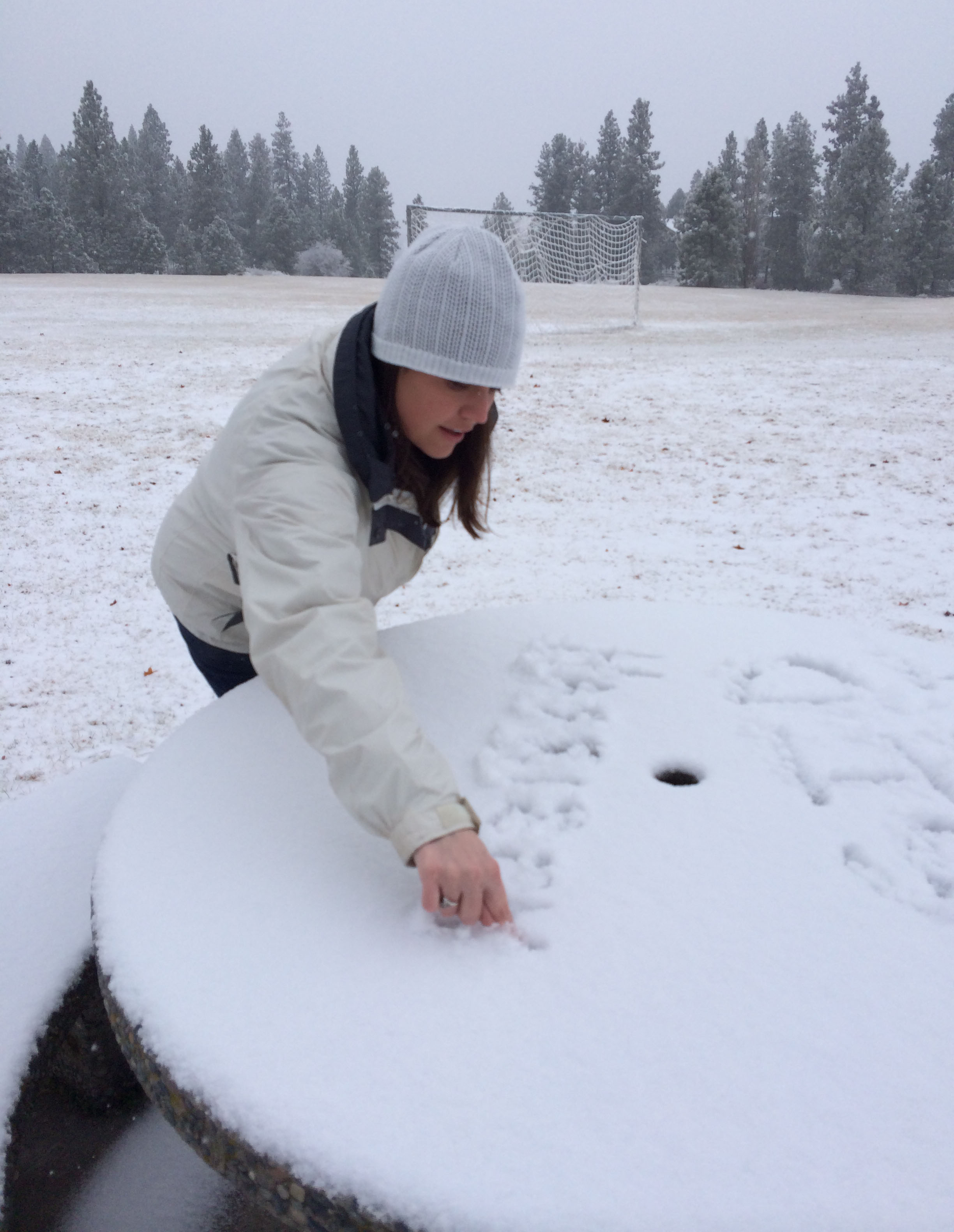 Sidney at Camelot Park writing the names of her niece and nephew into the snow.