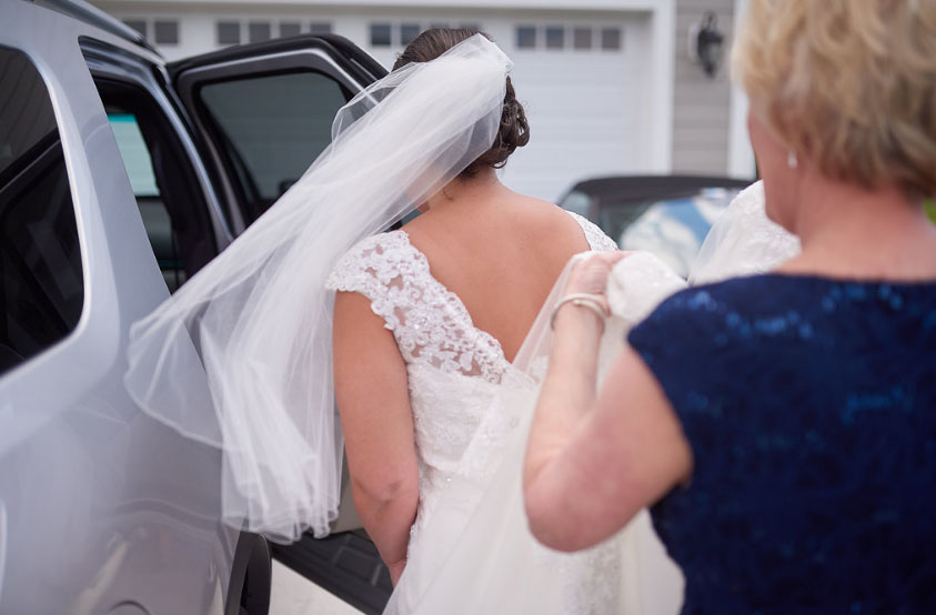 My mother-in-law, Brenda, helps her daughter into the car to go to the church (photo courtesy of Nicholas Gore Weddings Photography).