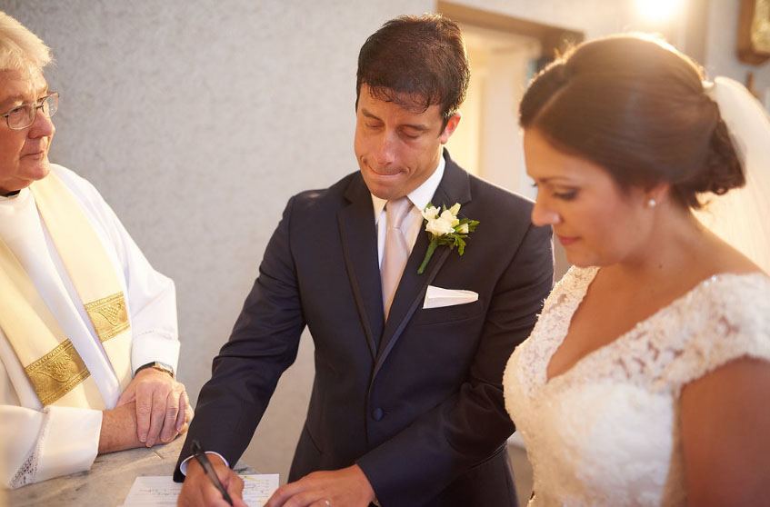 Fr. James LeBlanc, pastor of St. Andrew Parish in Myrtle Beach, looks on as we sign our marriage certificate. I had worn my ring for about 30 minutes up until this point. (photo courtesy of Nicholas Gore Weddings Photography).