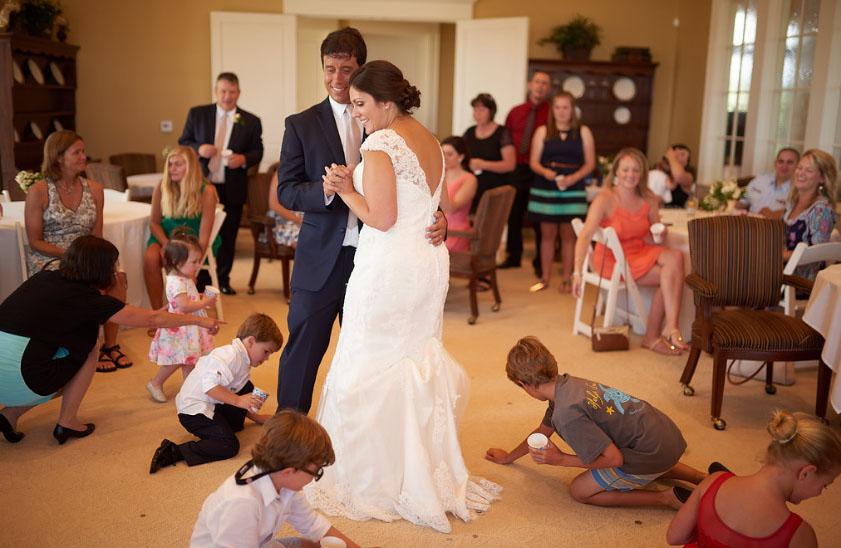 Kids get on hands and knees to pick up money during the Coin Dance (photo courtesy of Nicholas Gore Weddings Photography).