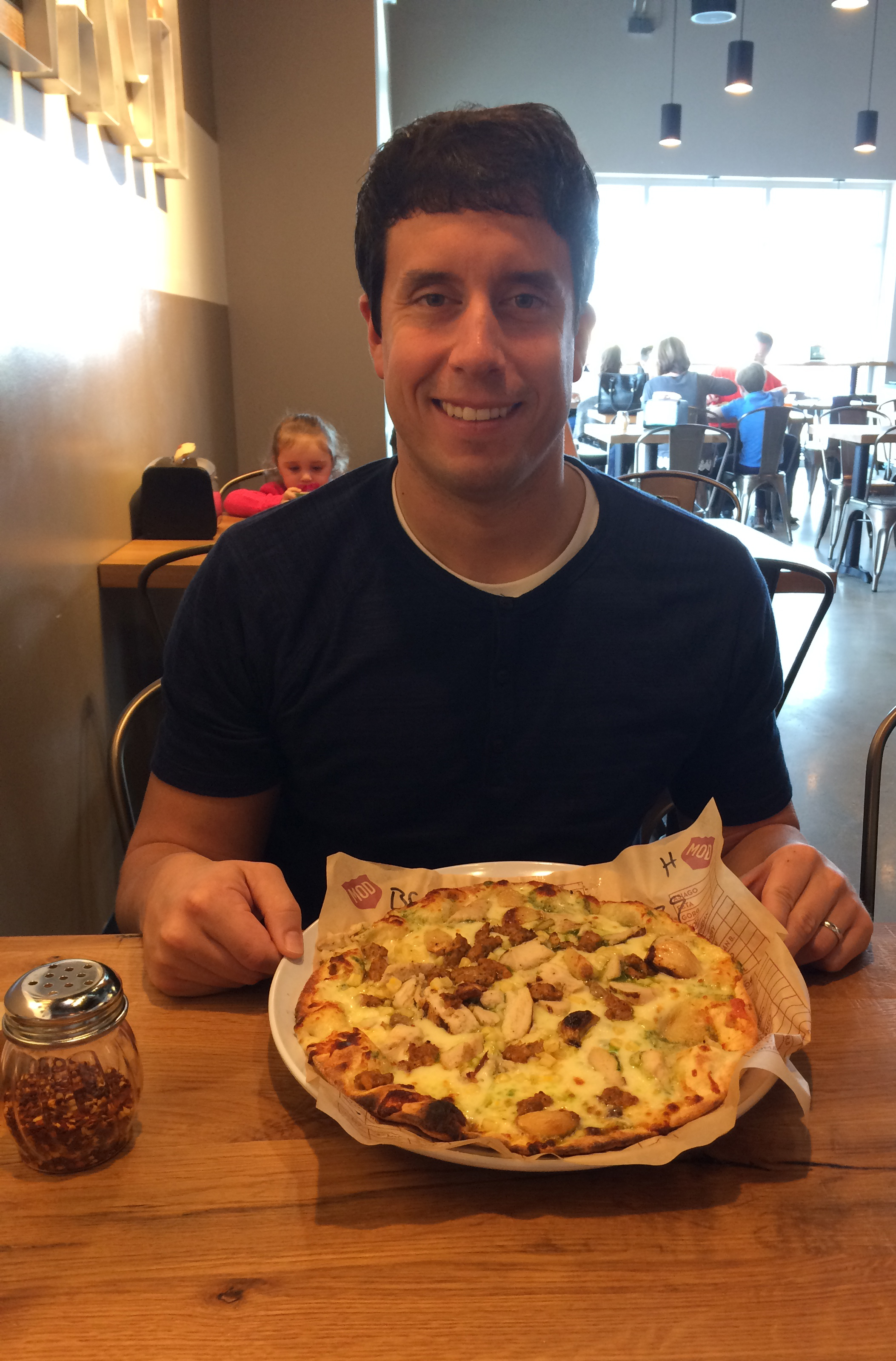 A photo of me with the pizza that I built from scratch. I really enjoyed MOD Pizza.